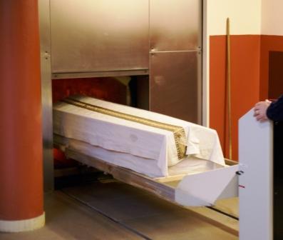 Invoer van een kist in een oven in Crematorium Ockenburgh