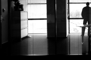 Image: View from inside a darkened home. A figure stands to the right hand side silhouetted in the window