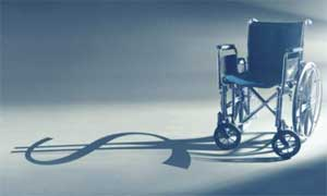 A wheelchair is lit from the right by a light which casts a shadow in the form of a dollar sign.