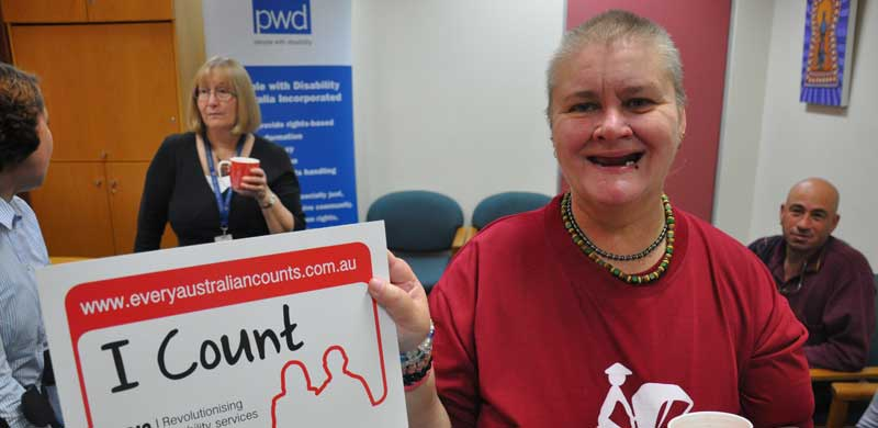 PWDA member, Lesley holding an NDIS Every Australian Counts sign with 'I Count' written on it. She is holding a mug of tea.