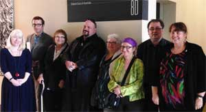 Image: photograph of eight people standing facing the camera and smiling. They stand insider under a sign which says Federal Court of Australia.