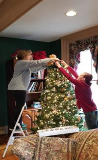 Peggy and April putting the topper on the Christmas tree