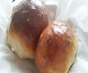 Two fluffy rolls on a white napkin in a basket