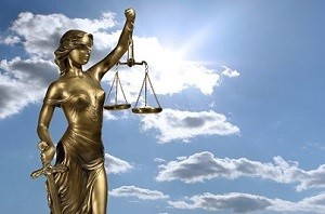Bronze blindfolded lady of justice holding up scales is positioned against a blue sky with white clouds