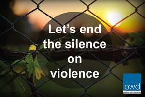 MAGE: A wire fence with sunshine and trees behind it. Over the top of the fence there is a dark shadow with white text on it that says Let's end the silence on violence.