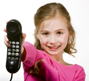 Child dressed in a pink shirt holding a mobile phone out towards the viewer