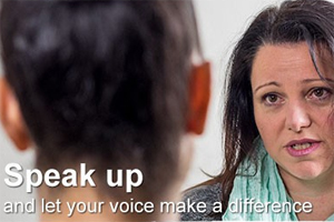 IMAGE: A woman speaks to another person. White letters spell out the words Speak Up and let your voice make a difference.
